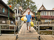 11 FEBRUARY 2015 - BANGKOK, THAILAND: A man walks down the to cross river ferry at the pier at Wat Kalayanamitr, a large Buddhist temple in the Thonburi section of Bangkok, next to the Catholic community of Santa Cruz. The temple was built in 1825, about 50 years after Santa Cruz Church was built.          PHOTO BY JACK KURTZ