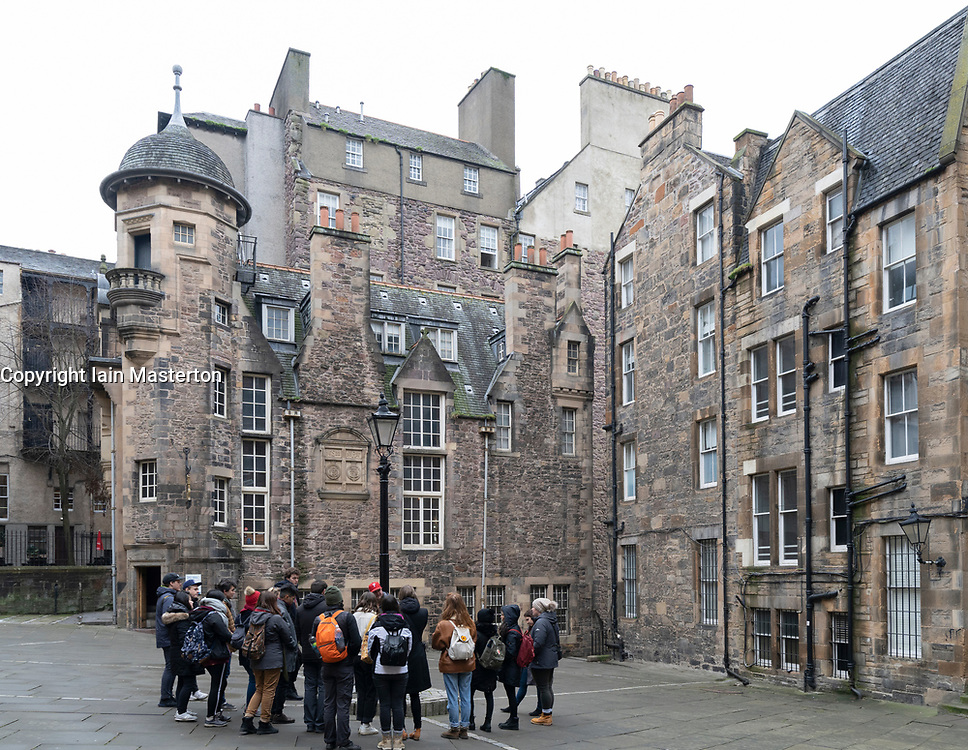 Tourists on walking tour at Makars' Court with the Writers Museum to rear in Edinburgh Old Town, Scotland, UK