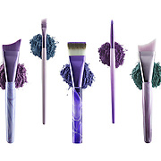 "Five cosmetic brushes from Anisa Internationals ""Spiral Fusion"" brush set, each brush set upon it's own loose pile of cosmetic powders."