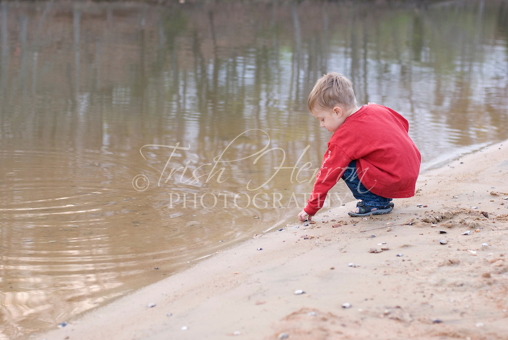 A small boy plays with rocks on a beach at the lake.