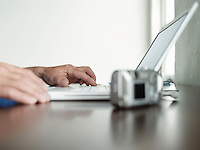 Man sitting at desk using laptop side view close-up of hands