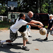 Derrick Washington, 14, of Beaufort, left, makes the steal against Leo Ferlo, 20, of Beaufort, center, while playing a game of twenty-one with friends Wesley Wiska, 11, right, and Andre Smith,11, not pictured, off of Baynard Road and Peacock Run in Beaufort on June 26, 2014.