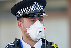 © Licensed to London News Pictures. 09/04/2020. London, UK. A police officer wears a protective face mask as he stands on duty outside St Thomas' Hospital in central London. Prime Minister Boris Johnson is spending his 5th day in the hospital after contracting the coronavirus. Photo credit: LNP