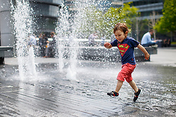 © Licensed to London News Pictures. 09/05/2016. London, UK. Xavier O'Farrell plays with fountains near City Hall in London whilst enjoying sunshine and warm weather on Monday, 9 May 2016. Photo credit: Tolga Akmen/LNP