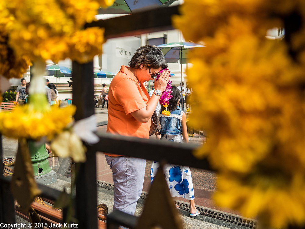 22 AUGUST 2015 - BANGKOK, THAILAND: Flower garland offerings left on the fence around Erawan Shrine frame a woman praying in the shrine. Erawan Shrine in Bangkok reopened Wednesday, August 19, after more than 20 people were killed and more than 100 injured in a bombing at the shrine Monday, August 17, 2015. The shrine is a popular tourist attraction in the center of Bangkok's high end shopping district and is an important religious site for Thais. No one has claimed responsibility for the bombing.             PHOTO BY JACK KURTZ