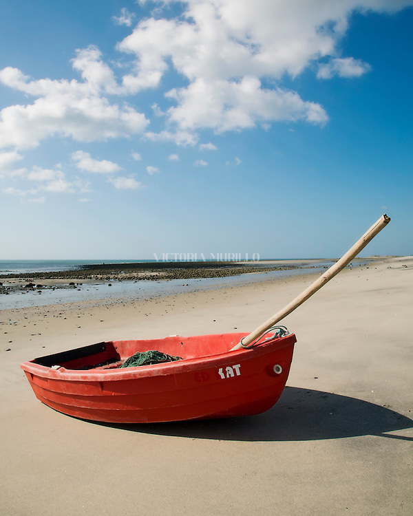 PUNTA BARCO, PANAMA - JANUARY 23: A small red boat lies on a sandy beach during a sunny day with blue skies. February 23, 2012. Punta Barco, Panamá. (Photo: Rubén Alfú / Istmophoto)
