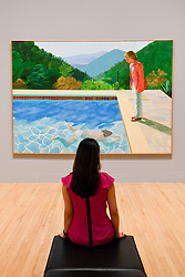 "© Licensed to London News Pictures. 06/02/2017. London, UK. A staff member views ""Portrait of an Artist (Pool with Two Figures)"" at the preview of the world's most extensive retrospective of the work of David Hockney at the Tate Britain, which will be on display 9 February to 29 May 2017. Photo credit : Stephen Chung/LNP"
