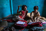 After waking up, Poonam, 10, (left) and her older sister Jyoti, 11, (right) are studying together inside their newly built home in Oriya Basti, one of the water-contaminated colonies in Bhopal, central India, near the abandoned Union Carbide (now DOW Chemical) industrial complex, site of the infamous '1984 Gas Disaster'.