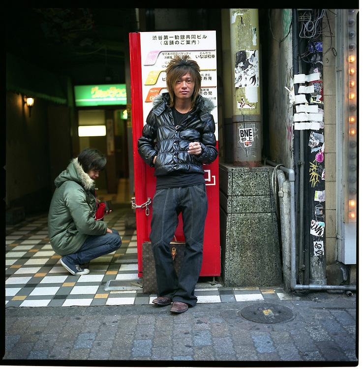 Young gal-O man watches foot traffic, Shibuya, Tokyo, Japan.