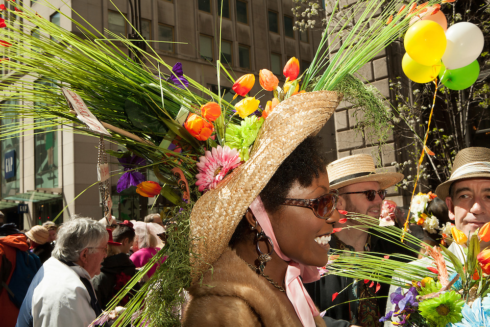 A woman wearing a straw hat with the apearance of a flower garden.