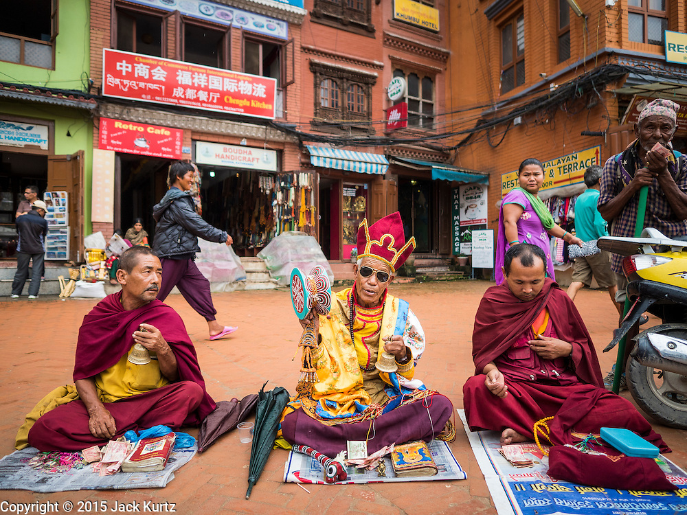 31 JULY 2015 - KATHMANDU, NEPAL: Tibetan Buddhist monks play traditional music and pray before the full moon procession at Bodhnath Stupa. Bodhnath Stupa in the Bouda section of Kathmandu is one of the most revered and oldest Buddhist stupas in Nepal. The area has emerged as the center of the Tibetan refugee community in Kathmandu. On full moon nights thousands of Nepali and Tibetan Buddhists come to the stupa and participate in processions around the stupa. The stupa was heavily damaged in the earthquake of 25 April 2015 and people are no longer allowed to climb on the stupa, now they walk around the base and pray with butter lamps.   PHOTO BY JACK KURTZ