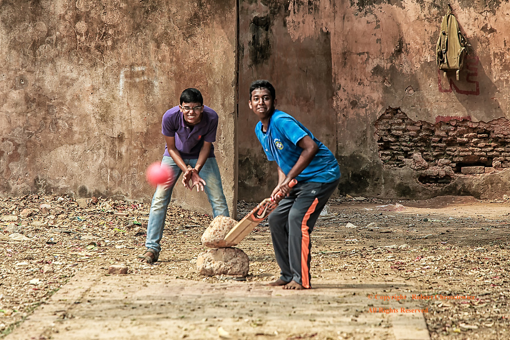 Batter's Up: A young man smiles in anticipation of batting the red ball being hurled his way in this makeshift cricket pitch, Dhaka Bangladesh.