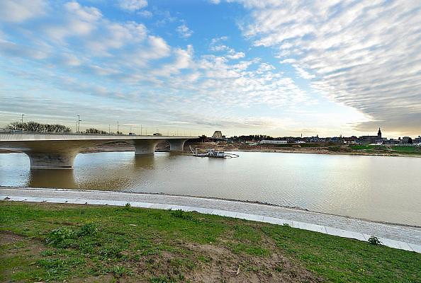 Nederland, Nijmegen, 23-11-2015 De 4 km. lange nevengeul aan de overkant van de Waal bij Lent nadert zijn voltooiing. Laatste werkzaamheden. Zicht op de verlengde Waalbrug die de betonprijs won. Grootste onderdeel van de vele werken van Rijkswaterstaat om bij hoogwater een betere waterafvoer in de rivier te hebben.  In precies drie jaar is het werk uitgevoerd.  Het is een omvangrijk project waarbij onder meer de pijlers van het spoorviaduct een bredere basis kregen omdat die straks in de loop van het water staan. Ook de n325 die vanaf de Waalbrug naar Arnhem loopt is over 400 meter opnieuw aangelegd omdat het talud vervangen wordt door een nieuwe brug met drie gracieuze pijlers. Het dorp veurlent komt op een kunstmatig eiland te liggen met twee bruggen als ontsluiting. Een voetgangersbrug en een andere, de Promenadebrug, voor normaal verkeer. Inmiddels begint de nieuwe kade aan de noordkant van deze geul vorm te krijgen. Ruimte voor de rivier, water, waal. In de nieuwe dijk wordt een drempel gebouwd die stapsgewijs water doorlaat en bij hoogwater overloopt. The Netherlands, Nijmegen Measures taken by Nijmegen to give the river Waal, Rhine, more space to flow during highwater and to prevent the risk of flooding. Room for the river. Reducing the level, waterlevel. Large project to create a new paralel gully, an extra flow of water, so the river can drain more water during highwater. Due to climate change and expected rise, increase of the sealevel, the Dutch continue to protect their land from the water. Foto: Flip Franssen