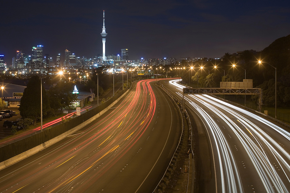 New Zealand, North Island, Auckland, Sky Tower rises above city skyline, with blurred lights of traffic on motorway at twilight on summer evening