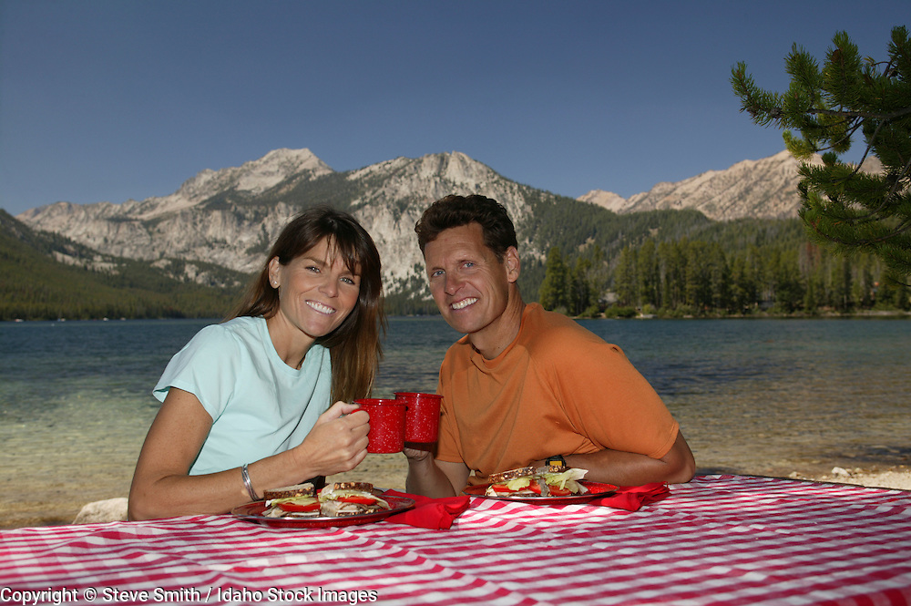 Idaho, Pettit Lake.  Couple enjoying a lakeside picnic north of Sun Valley in the Sawtooth Mountains.