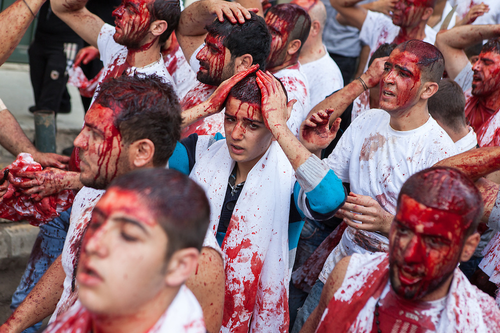 Shiite muslims, covered in their own blood, marching through the streets of Nabatieh, Lebanon, during the Day of Ashura (November 14, 2013). Wounds are self-inflicted by using traditional swords and knives. Some participants faint due to blood loss and are treated by paramedics in tents. Men, women, as well as children participate. The city of Nabatieh (a.k.a. Nabatiye, Nabatiyeh) is one of the few places where this particular ritual is still performed. It is even frowned upon by Hezbollah, who encourage people to donate blood at a local hospital instead.