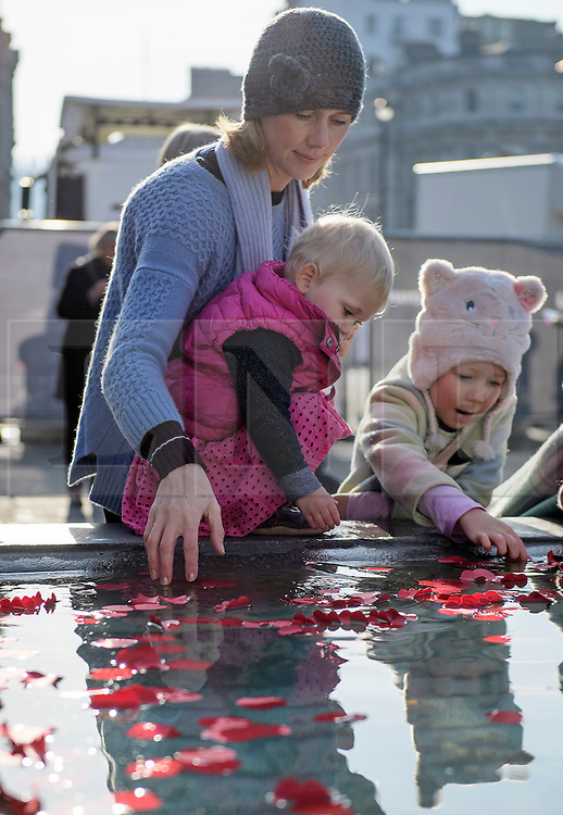 © Licensed to London News Pictures. 11/11/2016. London, UK. Sarah Vanderput and her daughters Lexi (aged one) and Jemila (aged 7) places poppies in to the fountain during Silence in the Square, a service held in Trafalgar Square, London to mark Remembrance Day. A minutes silence is held on the 11th hour of the 11th day of the 11th month, to recall the end of hostilities of World War I.  Photo credit: Ben Cawthra/LNP