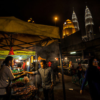 Resident buys food at night market stall in Kampung Baru, Kuala Lumpur, Malaysia, 8 April 2017. The night market sell various items like local food and agricultural products like vegetables, fruits, meat and other wet stuff, clothes and many more. It attracts a lot of people to visit because of affordable prices. The night market used to be a social gathering place among the villagers in the past. Night market culture in Kampung Baru still survives even though declining.