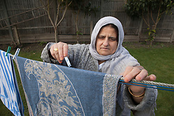 South Asian woman hanging up washing on line.