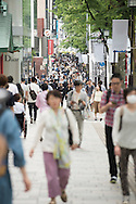 Japanese people walk down the busy street f Omotesando a fashionable shopping area in the capital city of Japan.