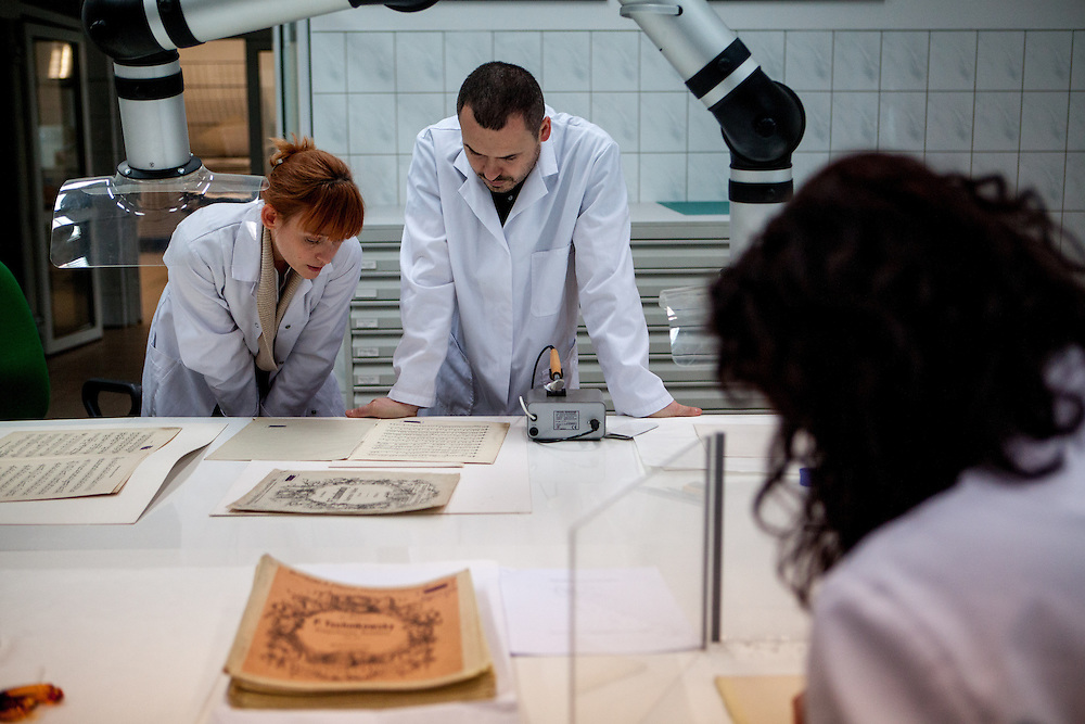 Nel Jastrzebiowska (left, working since 12 Years in the lab) and her colleague Miroslaw Maciaszczyk (11 years employeed) at the Auschwitz  Museum Preservation lab for documents, books and other historical papers. At the moment the employees work on note sheets of composer Tchaikovsky which had been lately found and were used by the prisoners orchestra in Auschwitz. The Museum Preservation Department is responsible for protecting everything that remains at the Auschwitz-Birkenau Concentration Camp site.