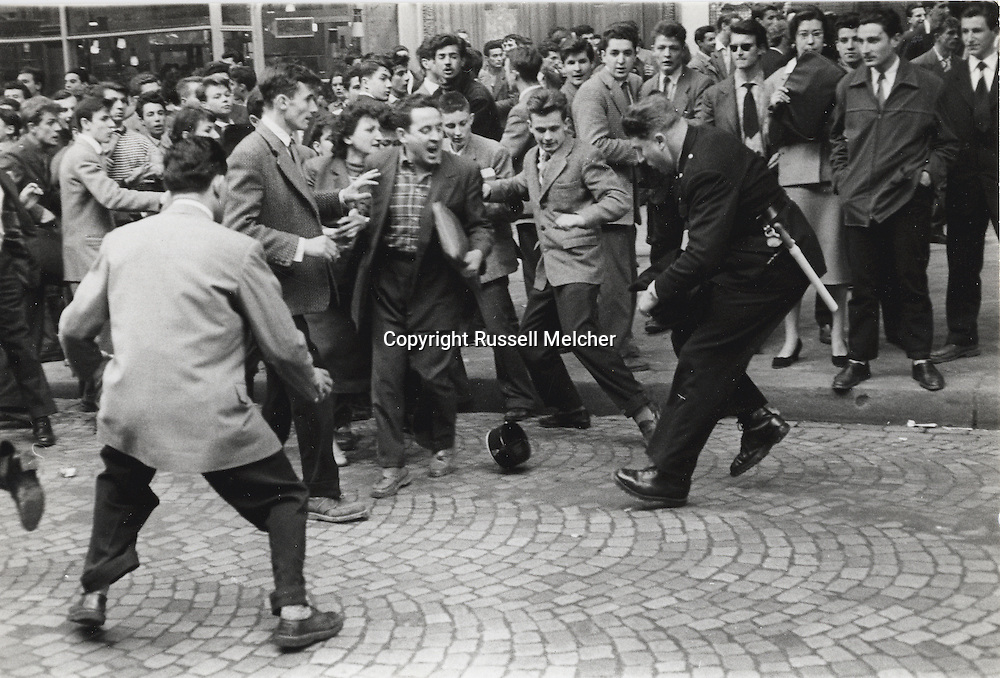 Paris 1955. Latin Quarter demonstrations. Policeman loses his hat in a struggle.<br />