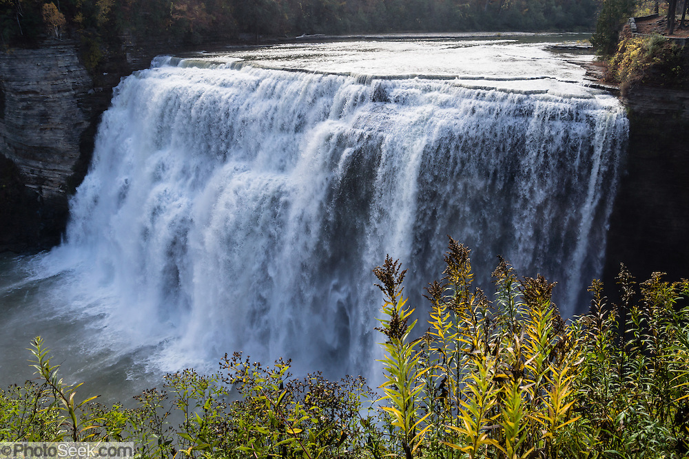 "Middle Genesee Falls, Portage Canyon, Letchworth State Park, Portageville, New York, USA. In Letchworth State Park, renowned as the ""Grand Canyon of the East,"" the Genesee River roars northeast through a gorge over three major waterfalls between cliffs as high as 550 feet, surrounded by diverse forests which turn bright fall colors in the last three weeks of October. The large park stretches 17 miles between Portageville and Mount Morris in the state of New York, USA. Drive or hike to many scenic viewpoints along the west side of the gorge. The best walk is along Gorge Trail #1 above Portage Canyon from Lower Genesee Falls (70 ft high), to Inspiration Point, to Middle Genesee Falls (tallest, 107 ft), to Upper Genesee Falls (70 ft high). High above Upper Falls is the railroad trestle of Portageville Bridge, built in 1875, to be replaced 2015-2016. Geologic history: in the Devonian Period (360 to 420 million years ago), sediments from the ancestral Appalachian mountains eroded into an ancient inland sea and became the bedrock (mostly shales with some layers of limestone and sandstone plus marine fossils) now exposed in the gorge. Genesee River Gorge is very young, as it was cut after the last continental glacier diverted the river only 10,000 years ago. The native Seneca people were largely forced out after the American Revolutionary War, as they had been allies of the defeated British. Letchworth's huge campground has 270 generously-spaced electric sites."