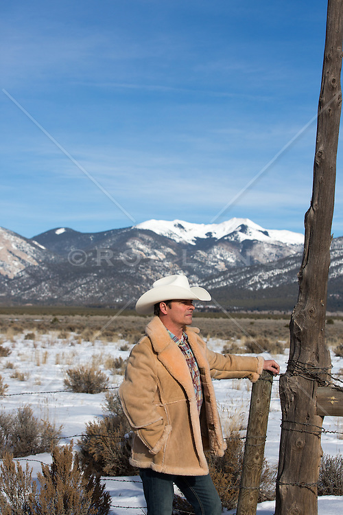 cowboy on a snow covered ranch with mountain views