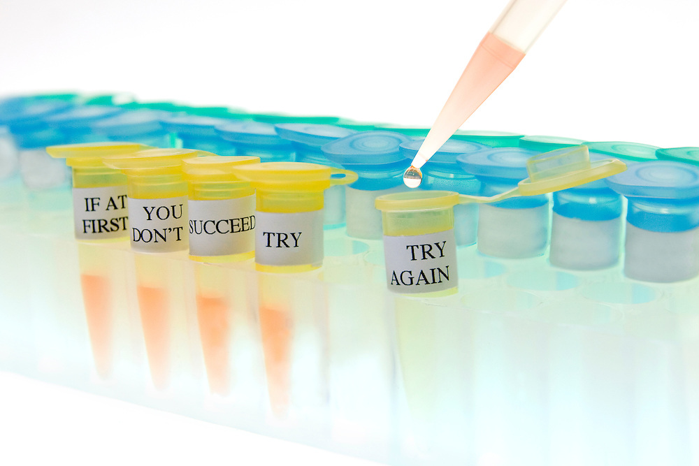 """The phrase """"If at first you don't succeed, try, try again"""" is written out on a number of microtubes in a rack."""