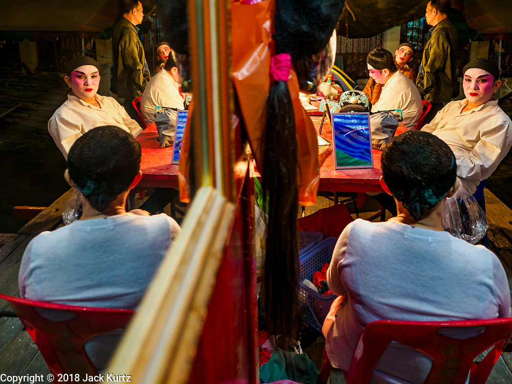 """12 JANUARY 2018 - BANGKOK, THAILAND:      Chinese opera performers relax before a performance at the Chaomae Thapthim Shrine in the Dusit district of Bangkok. Many Chinese shrines and temples host Chinese operas during the Lunar New Year. Lunar New Year is 16 February this year and opera troupes are starting their holiday engagements at local Chinese temples and shrines. The new year will be the """"Year of the Dog."""" Chinese New Year, also called Lunar New Year or Tet, is widely celebrated in Chinese communities around the world. Thailand has a large Chinese community and Lunar New Year is an important holiday.   PHOTO BY JACK KURTZ"""