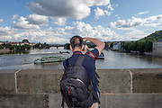 A tourist is taking  photographs of ships sailing on Vltava river underneath Charles Bridge. The Charles Bridge (Czech: Karlův most) is a famous historic bridge that crosses the Vltava river in Prague, Czech Republic and is probably the Nr.1 tourists magnet in the city.