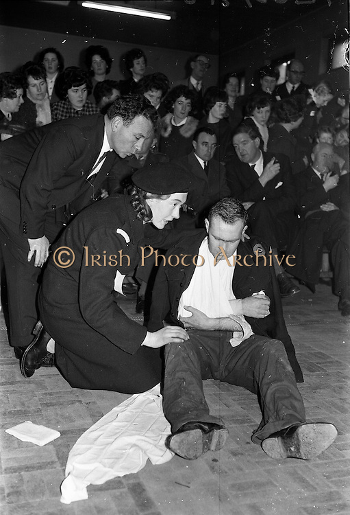 31/03/1963<br /> 03/31/1963<br /> 31 March 1963<br /> Civil Defence Competitions at Jervis Street Hospital, Dublin. Dr. Jacobson watching Miss Anne Carolan (Cabra team) at work on a casualty.