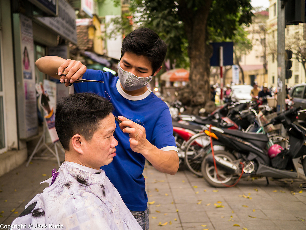 30 MARCH 2012 - HANOI, VIETNAM:   A barber gives a man a haircut at his sidewalk barbershop in the Old Quarter of Hanoi, the capital of Vietnam.  PHOTO BY JACK KURTZ