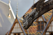 Gargoyle at Les Hospices de Beaune, or Hotel-Dieu de Beaune, a charitable almshouse and hospital for the poor, built 1443-57 by Flemish architect Jacques Wiscrer, and founded by Nicolas Rolin, chancellor of Burgundy, and his wife Guigone de Salins, in Beaune, Cote d'Or, Burgundy, France. The buildings, set around an internal courtyard, are in Northern Renaissance and Flamboyant Gothic style, with half-timber galleries, ornate rooftops with Burgundian glazed tiles in geometric patterns and dormer windows. The hospital was run by the nuns of the order of Les Soeurs Hospitalieres de Beaune, and remained a hospital until the 1970s. The building now houses the Musee de l'Histoire de la Medecine, or Museum of the History of Medicine, and is listed as a historic monument. Picture by Manuel Cohen