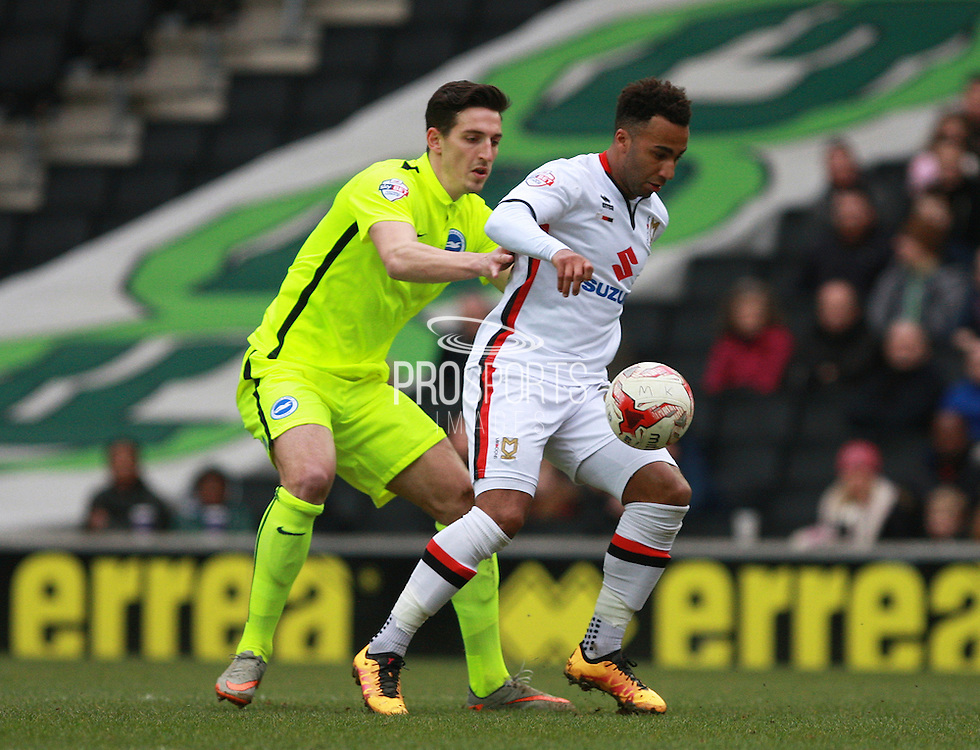 Milton Keynes Dons striker Nicky Maynard shields the ball from Brighton central defender Lewis Dunk during the Sky Bet Championship match between Milton Keynes Dons and Brighton and Hove Albion at stadium:mk, Milton Keynes, England on 19 March 2016. Photo by Bennett Dean.
