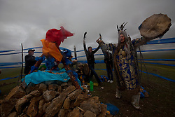 Mongolian Shaman Batgerel Batmunkh leads worshippers around the 'Ovoo' or 'sacred stone' site during a Shaman ceremony on Black Mountain Head in Nalaikh district of Ulan Bator in Mongolia, 06 July 2012. The Shaman ceremony is held for a family to give offerings to the spirits of nature and to bring good karma to the members of family. The scarves of color blue is symbolic of the 'open sky' or 'Tengri' while red represents 'fire'; orange for 'sand' and white for 'milk'. Shamanism comes from the term 'shamans' that refers to priests or mediums that acts as vessels for spirits, gods and demons to communicate with the human world. In Mongolia, they adhere to the ancient beliefs of Tengrism, where spirits live in all of nature, in the sun, moon, lakes, rivers, mountains, and trees.