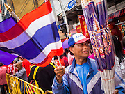 """19 FEBRUARY 2015 - BANGKOK, THAILAND: A man sells Thai flags and the purple flag which is the personal flag of Princess Maha Chakri Sirindhorn, who opened Chinese New Year festivities in Bangkok. 2015 is the Year of Goat in the Chinese zodiac. The Goat is the eighth sign in Chinese astrology and """"8"""" is considered to be a lucky number. It symbolizes wisdom, fortune and prosperity. Ethnic Chinese make up nearly 15% of the Thai population. Chinese New Year (also called Tet or Lunar New Year) is widely celebrated in Thailand, especially in urban areas that have large Chinese populations.    PHOTO BY JACK KURTZ"""