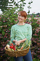 Woman holding fruit and vegetable basket in garden portrait