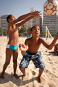 TWO YOUNG BOYS SHOWING FOOTBALL SKILLS ON COPACBANA BEACH RIO KEEPY UPPYS