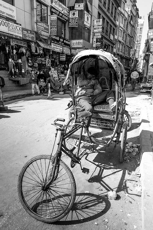 A rickshaw driver in Kathmandu catches a quick nap