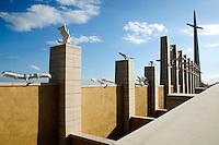 """È stata inaugurata il 1° luglio 2004, la nuova Chiesa di San Pio da Pietrelcina progettata dall'architetto Renzo Piano. Esattamente 45 anni prima, nel 1959,  veniva inaugurata la chiesa """"grande"""" di Santa Maria delle Grazie. .Sorta a fianco del santuario e convento in cui visse il frate, ha la forma di una conchiglia e la sua pianta ricorda quella della spriale archimedea. Enormi archi parto dal perimetro esterno e terminano nel fulcro della """"conchiglia"""" dove è posto l'altare. Possenti staffe d'acciaio, ancorate agli archi, sorreggono la volta che ricoperta di rame preossidato espone alla vista un intenso un colore verde-rame.   .Con i suoi 6000 mq, è la seconda chiesa più grande in Italia per dimensioni, dopo il Duomo di Milano. Può ospitare oltre 7000 persone e per la sua realizzazione sono state impiegati 30.000 metri cubi di calcestruzzo, 1.320 blocchi in pietra di Apricena, 70.000 metri cubi di scavo in roccia, 60.000 chili di acciaio, 500 mq di vetro, 19.500 mq di rame preossidato. Ogni anno è meta di oltre sei milioni di pellegrini..Nella foto la struttura che fiancheggia la chiesa composta da un'alta croce e una serie di otto campanili stilizzati con altrettante campane. Su aclune colonne sono poste aclune sagome raffiguranti bianche colombe."""