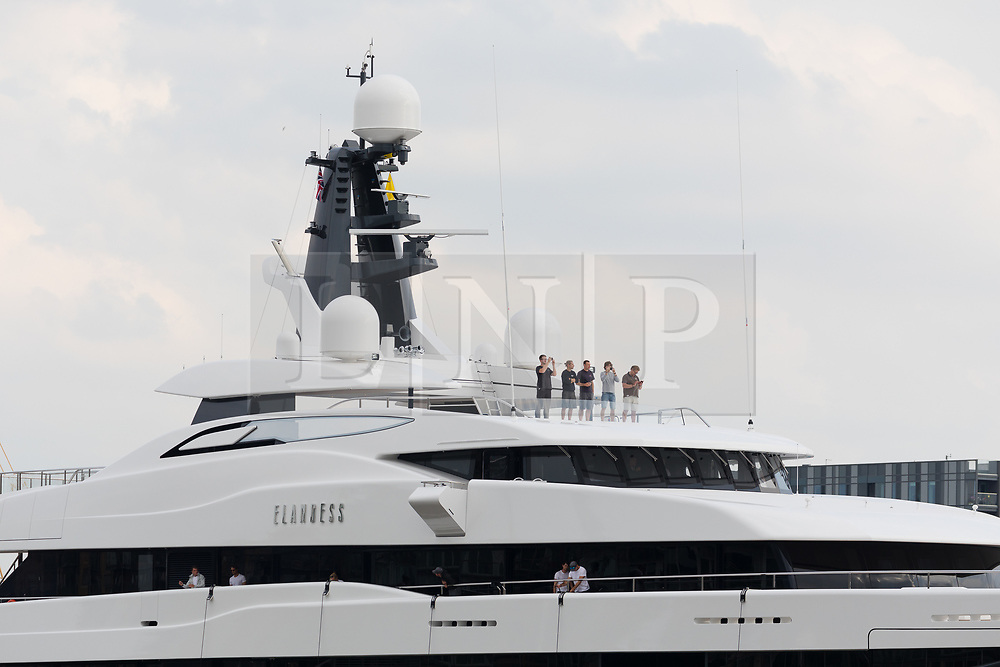 © Licensed to London News Pictures. 04/07/2018. London, UK.  People on board take photographs as the new 243 feet long superyacht, Elandess arrives in London for the first time ever on the River Thames and moors at HMS President, the Royal Navy Reserve Unit next to St Katharine Docks and Tower Bridge this evening. Elandess was built at the Abeking and Rasmussen shipyard in Germany, launched in May 2018 and has just completed sea trials ahead of its London visit. Elandess has an axe-bow, dark hull and low-slung superstructure. There are a variety of entertaining communal spaces, from the 8 x 2.5-metre superyacht swimming pool located on the massive sun deck to the Nemo Lounge with portholes below the waterline and an observation lounge on the upper deck. Guest accommodation includes six staterooms, including the master suite which is placed forward on the main deck with an observation lounge directly above on the upper deck.  Photo credit: Vickie Flores/LNP