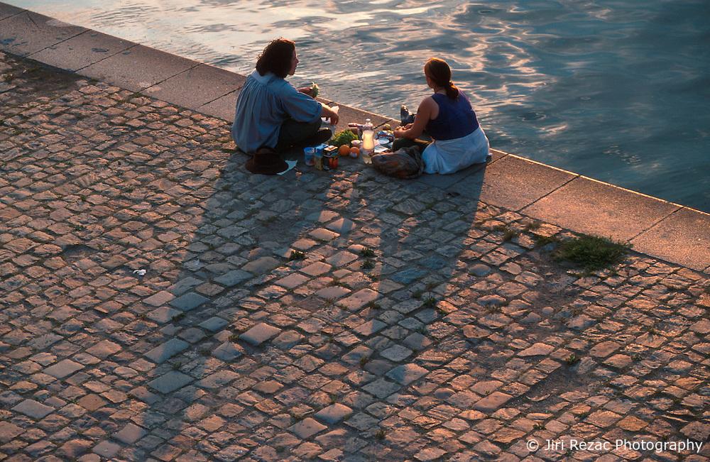 CZECH REPUBLIC PRAGUE AUG97 - Two picknickers sit on the bank of the river Vltava in Prague during sunset.. . jre/Photo by Jiri Rezac. . © Jiri Rezac 1997. . Tel:   +44 (0) 7050 110 417. Email: jiri@jirirezac.com. Web:   www.jirirezac.com