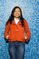 An early 30's / late 20's Asian woman (Japanese/Filipino) smiling in front of a torquoise tiled wall..Model Release: 20070513_MR_A