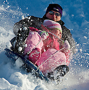 BLASTING THROUGH WINTER--Showing Winter Olympics form are Samantha Noppenberger and he uncle, Steven Oppenberger, as they blast through a snow mound and fly down a McDaniel College golf course hill.
