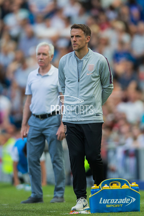 Phil Neville, Head Coach of England FC with Tom Sermanni, Head Coach of New Zealand FC in the background during the FIFA Women's World Cup UEFA warm up match between England Women and New Zealand Women at the American Express Community Stadium, Brighton and Hove, England on 1 June 2019.