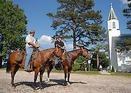 22 MAY 2010 -- JAPAN, Mo. -- Case Blankenship (left, CQ) and Chad Trendle (center, CQ) arrive on horseback at Holy Martyrs of Japan Church in unincorporated Japan, Mo. for a special horse and mule service Saturday, May 22, 2010. More than 25 church members at the rural parish rode to services, and gathered afterward with other parishioners for a chuck wagon meal prepared by Bev and Bill Turner. Image © copyright 2010 by Sid Hastings.