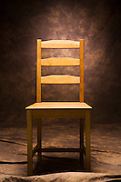 An empty wooden chair on a painted canvass background