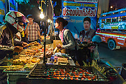 23 NOVEMBER 2013 - BANGKOK, THAILAND: A grilled meat vendor sells food to people going into a Prathom Bunteung Silp mor lam troupe show in Bangkok. Mor Lam is a traditional Lao form of song in Laos and Isan (northeast Thailand). It is sometimes compared to American country music, song usually revolve around unrequited love, mor lam and the complexities of rural life. Mor Lam shows are an important part of festivals and fairs in rural Thailand. Mor lam has become very popular in Isan migrant communities in Bangkok. Once performed by bands and singers, live performances are now spectacles, involving several singers, a dance troupe and comedians. The dancers (or hang khreuang) in particular often wear fancy costumes, and singers go through several costume changes in the course of a performance. Prathom Bunteung Silp is one of the best known Mor Lam troupes in Thailand with more than 250 performers and a total crew of almost 300 people. The troupe has been performing for more 55 years. It forms every August and performs through June then breaks for the rainy season.              PHOTO BY JACK KURTZ