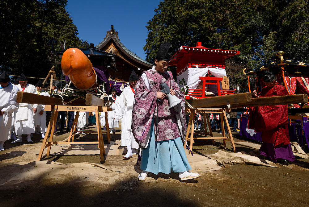 A Shinto priest walks in front of a wooden phallus during Honen-sai, a fertility festival at Tagata Shrine in Komaki, Aichi Prefecture, Japan. The traditional Shinto festival celebrates fertility and a bountiful harvest. The principal offering during the festival is a large wooden phallus. Each year a craftsman carves a new phallus from a Japanese cypress tree. It measures almost 2.4 meters (13 feet) long and weights 280kg (620 pounds).